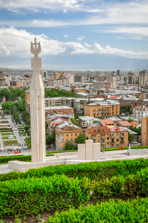 Photo of large monument surrounded by greenery and buildings of capital city Yerevan in Armenia.