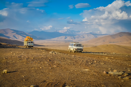 Photo of two large cars driving through empty plains and road to Kabul in Afghanistan.