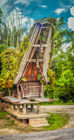 Large ancestral house also called tongkonan, typical of boat-shaped and large saddleback roof and colourful patterns in Sangalla, Toraja region in southern Sulawesi, Indonesia. Stock Photo