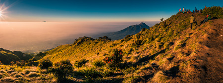 Panoramic photo of mountains surrounding Mount Merbabu and hikers at top during sunrise near Yogya in central Java province in Indonesia. In this region, one can only meet people from isolated local tribes. Stock Photo