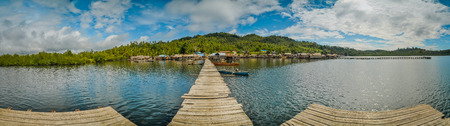 Photo of wooden jetty, sea and coast with houses in diistance in Katupat in Sulawesi, Indonesia. Stock Photo