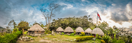 Panoramic view of row of traditional houses with straw roofs in village with flag in Dani circuit near Wamena, Papua, Indonesia. Standard-Bild