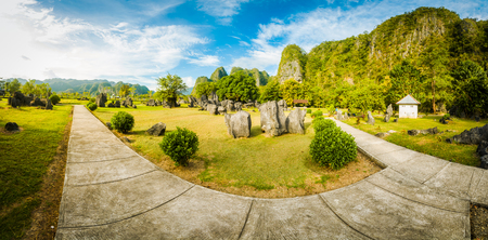 Photo of greenery of large garden with stone path and surrounding stones in Maros in southwestern Sulawesi in Indonesia.
