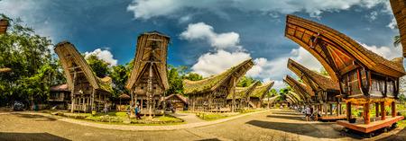Panoramic photo of tongkonans with saddleback roofs and small square in Kete Kesu, Toraja region in Sulawesi, Indonesia.