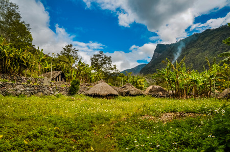 Small houses with straw roofs in village surrounded by greenery and high mountains in Dani circuit near Wamena, Papua, Indonesia.