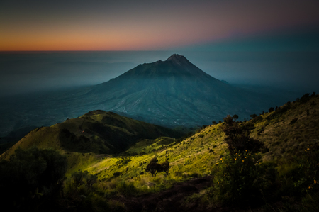 Scenic aerial view of dormant stratovolcano, Mount Merbabu, and surrounding mountains near Yogya in central Java province in Indonesia. In this region, one can only meet people from isolated local tribes.
