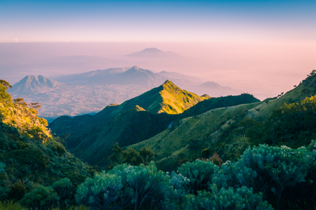 Photo of mountains surrounding Mount Merbabu in morning sunlight near Yogya in central Java province in Indonesia. In this region, one can only meet people from isolated local tribes. Stock Photo