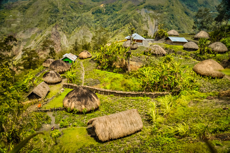 Photo of traditional village houses with straw roofs in village surrounded by high mountains in Dani circuit near Wamena, Papua, Indonesia.