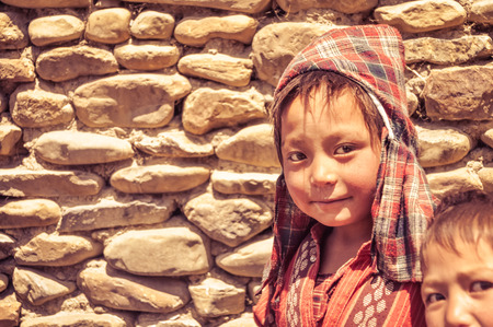 headcloth: Dolpo, Nepal - circa June 2012: Small brown-haired boy with checked red headcloth and red shirt with nice brown eyes in Dolpo, Nepal. Documentary editorial.