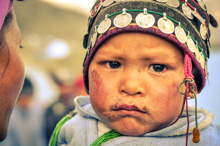 frowns: Dolpo, Nepal - circa May 2012: Small child with cap with coins on head has dirt on face and frowns to photocamera with black eyes in Dolpo, Nepal. Documentary editorial.