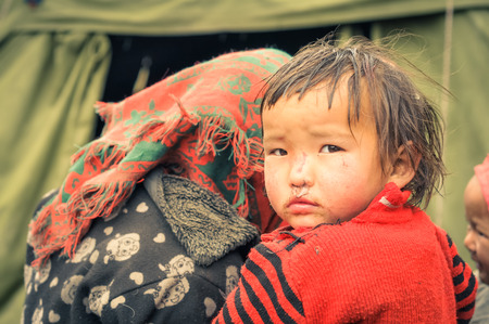 Dolpo, Nepal - circa June 2012: Small brown-haired girl in red sweater looks over shoulder to photocamera with brown eyes in Dolpo, Nepal. Documentary editorial.
