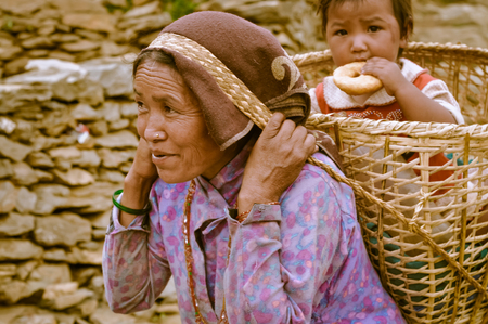 headcloth: Beni, Nepal - circa May 2012: Native woman with headcloth carries basket on her back with her child in it who eats cake and she walks up hill in Beni, Nepal. Documentary editorial.