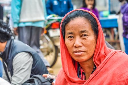 Bohdgaya, Bihar - circa January 2012: Woman with nice face has pink hood on her head during teachings in Bohdgaya, Bihar. Documentary editorial.
