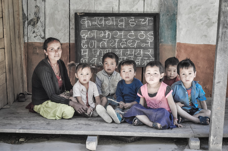 Kanchenjunga Trek, Nepal - circa May 2012: Teacher sits with children on ground during learning of letters of alphabet and they look to photocamera in Kanchenjunga Trek, Nepal.