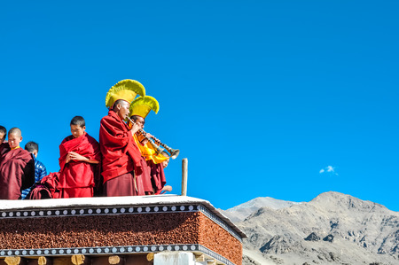Thiksey, Ladakh - circa November 2011: Monks with traditional big yellow hats stand at rooftop and play trumpets during Thiksey festival in Ladakh. Documentary editorial. Stock Photo
