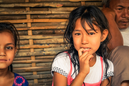 Damak, Nepal - circa May 2012: Young girl with long brown hair and with finger in her mouth looks curiously to photocamera at Nepali refugee camp in Damak, Nepal. Documentary editorial.