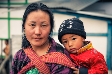 arunachal pradesh: Khinmey Gompa and Ugyenling Temple, Arunachal Pradesh - circa February 2012: Woman with black hair poses with her young son in Khinmey Gompa, Arunachal Pradesh. Documentary editorial.
