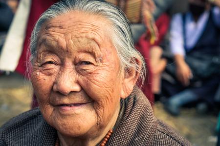 Bohdgaya, Bihar - circa January 2012: Older woman with grey hair and wrinkled face during teachings in Bohdgaya, Bihar. Documentary editorial.
