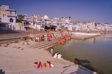 Pushkar, Rajasthan - circa December 2011: People dressed in colourful clothes handwash their clothes in river in Pushkar, Rajasthan. Documentary editorial.