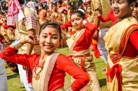 Guwahati, Assam - circa abril de 2012: joven nativa en sari rojo y amarillo con punto rojo en la frente durante la danza en el tradicional festival de Bihu en Guwahati, Assam. Editorial documental. Foto de archivo - 71003370