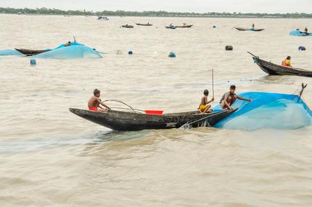 Sunderban, Bangladesh - circa July 2012: Young boys sit in wooden boat on river and fish in Sunderban, Bangladesh. Documentary editorial.