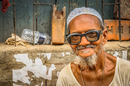 Dhaka, Bangladesh - circa July 2012: Old smiling man with white beard sits on stone bench and sells hammers and scissors in street in Dhaka, Bangladesh. Documentary editorial.