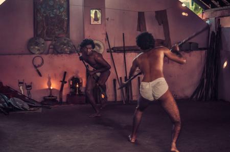 Thallashery, Kerala - vers février 2012: deux hommes à moitié nus tiennent une lance et interprètent le Kalaripayattu, forme d'art martial réputée pour être la plus ancienne du genre au monde. Documentaire éditorial. Éditoriale