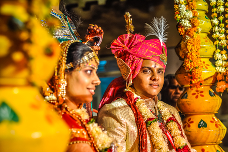 Bikaner, Rajasthan - circa December 2011: Young groom wears red turban during wedding ceremony in Bikaner, Rajasthan. Smiling bride sits next to him. Documentary editorial.
