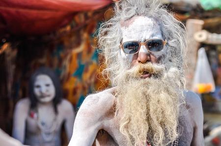 hinduist: Ganga Sagar, West Bengal - circa January 2012: Man with white powder on his body and long grey beard wears sunglasses and looks to photocamera in Ganga Sagar, West Bengal. Documentary editorial. Editorial
