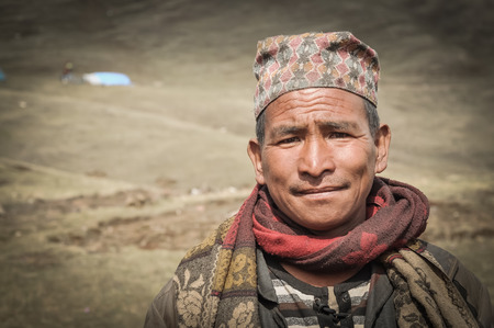 frowns: Dolpo, Nepal - circa May 2012: Native man with cap on his head and red scarf around neck frowns because of sunshine in Dolpo, Nepal. Documentary editorial. Editorial