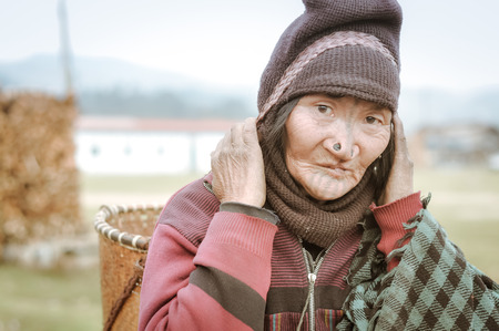 Ziro, Arunachal Pradesh - circa March 2012: Photo of Apatani woman with typical tattoo and large nose plugs who carries wicker basket in Ziro, Arunachal Pradesh. Documentary editorial. Editorial