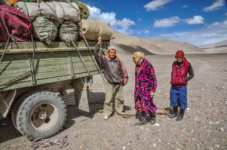 Karakul, Tajikistan - circa September 2011: Native people stand next to lorry with heavy load in Karakul, Tajikistan. Documentary editorial. Editorial