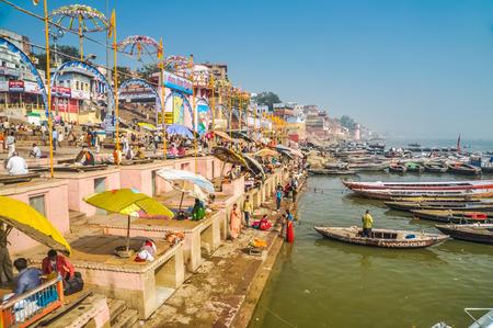 uttar pradesh: Varanasi, Uttar Pradesh - circa January 2012: People relax under umbrellas by river in Varanasi, Uttar Pradesh. Documentary editorial. Editorial