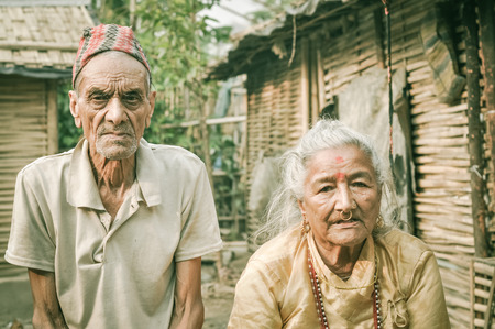 frowns: Damak, Nepal - circa May 2012: Old man with wrinkles on his face and with cap on his head frowns and poses with woman at Nepali refugee camp in Damak, Nepal. Documentary editorial.