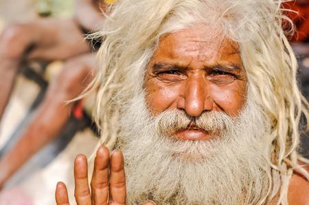 hinduist: Ganga Sagar, West Bengal - circa January 2012: Older man with long white beard and hair waves to photocamera in Ganga Sagar, West Bengal. Documentary editorial. Editorial