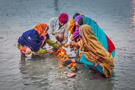 hinduist: Ganga Sagar, West Bengal - circa January 2012: People kneel and light up orange candles in Ganga Sagar, West Bengal. Documentary editorial.