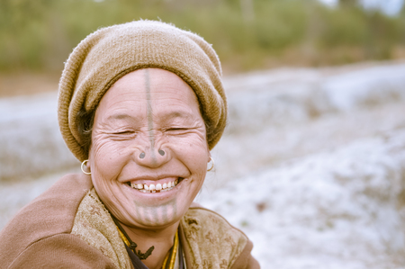 Ziro, Arunachal Pradesh - circa March 2012: Photo of smiling Apatani woman with tattoo on her face and nose plugs in Ziro, Arunachal Pradesh. Documentary editorial.