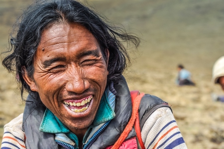 joyfully: Dolpo, Nepal - circa June 2012: Native black-haired man dressed in jacket sits on ground and laughs joyfully in Dolpo, Nepal. Documentary editorial.
