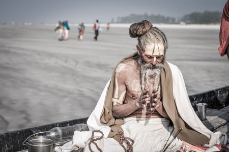 hinduist: Ganga Sagar, West Bengal - circa January 2012: Native man in white coat and with yellow colour on forehead sits in boat and prays in Ganga Sagar, West Bengal. Documentary editorial.