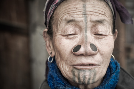 arunachal pradesh: Ziro, Arunachal Pradesh - circa March 2012: Photo of Apatani woman with tattoo on her face and large nose plugs with closed eyes in Ziro, Arunachal Pradesh. Documentary editorial.