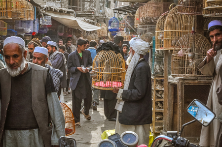 Kabul, Afghanistan - circa October 2011: Photo of marketplace full of shopping people in Old town, old city part in Kabul. In this market people can buy and sell birds in cages. Documentary editorial. Editorial