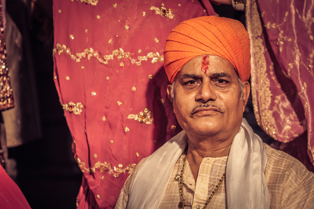 Bikaner, Rajasthan - circa December 2011: Photo of brides father in white with orange turban and colour on his forehead during wedding ceremony in Bikaner, Rajasthan. Documentary editorial. Editorial