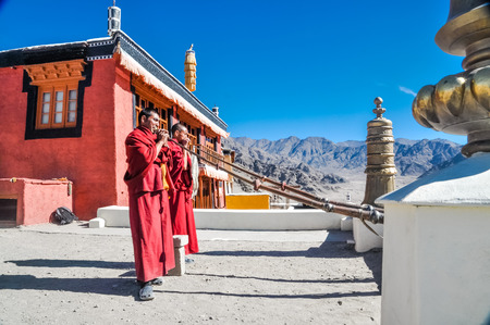 Thiksey, Ladakh - circa November 2011: Photo of two monks dressed in red blowing horns on roof as morning ceremony at Thiksey monastery, Ladakh. Documentary editorial. Editorial