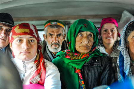 Khorog, Tajikistan - circa September 2011: People sit in car and some of them look to photocamera and smile in Khorog, Tajikistan. Documentary editorial.