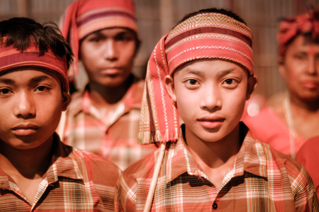 cintillos: Guwahati, Assam - circa April 2012: Young native boys in orange costumes and with headbands look to photocamera at Bihu festival in Guwahati, Assam. Documentary editorial. Editorial