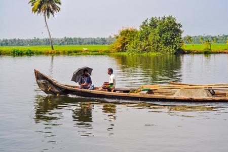 Alleppey Backwaters, Kerala - circa February 2012: Native men sit in wooden boat in beautiful countryside of Alleppey Backwaters in Kerala. One of them holds black umbrella. Documentary editorial.