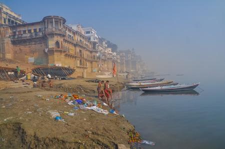 uttar pradesh: Varanasi, Uttar Pradesh - circa January 2012: Men stand by river near ships in foggy morning in Varanasi, Uttar Pradesh. Documentary editorial. Editorial