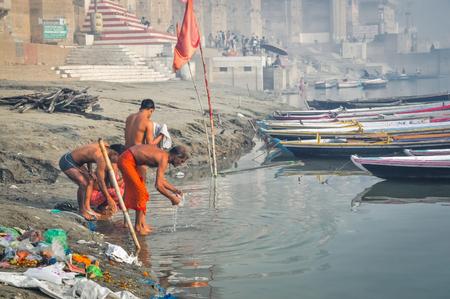 uttar pradesh: Varanasi, Uttar Pradesh - circa January 2012: Men wash themselves in river during foggy morning in Varanasi, Uttar Pradesh. Documentary editorial. Editorial