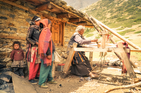 Dolpo, Nepal - circa June 2012: Old grey-haired woman in brown dress weaves on wooden loom outside her stone house and young girls watch her in Dolpo, Nepal. Documentary editorial. Editorial