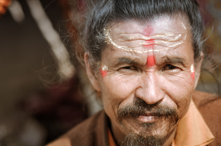 hinduist: Ganga Sagar, West Bengal - circa January 2012: Older man with red and yellow colour on forehead in Ganga Sagar, West Bengal. Documentary editorial. Editorial